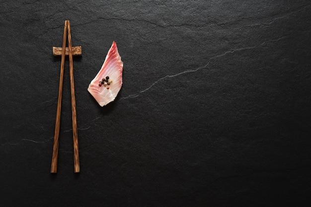 Astronautyczny drewniany chopstick z rybim plasterkiem na czerń marmuru tle