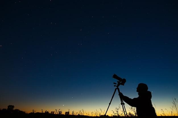 Astronom fotografuje nocne rozgwieżdżone niebo aparatem cyfrowym za pomocą statywu.