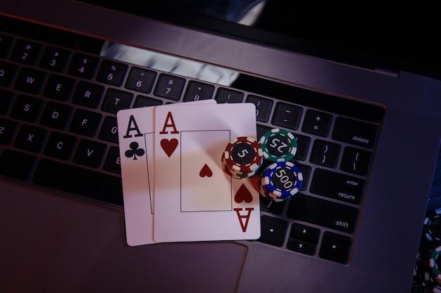 Asy z żetonami do gry na klawiaturze laptopa.