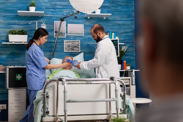 Asystenci pomocy społecznej pomagając chorej hospitalizowanej starszej kobiecie oddychać