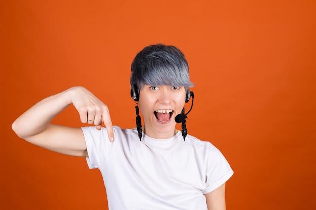Asystent call center ze słuchawkami na pomarańczowej ścianie wygląda na szczęśliwego i pozytywnego z pewnym uśmiechem, wskazując palcem w dół