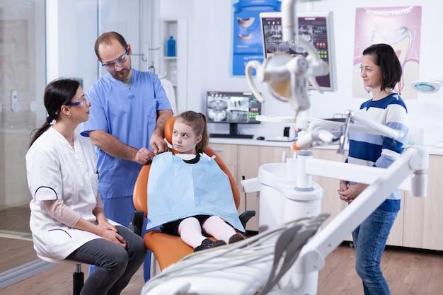Asystent dentysty przygotowujący dziecko pacjenta do badania zęba w gabinecie stomatologicznym. dziecko z matką podczas badania zębów u stomatologa siedzącego na krześle.