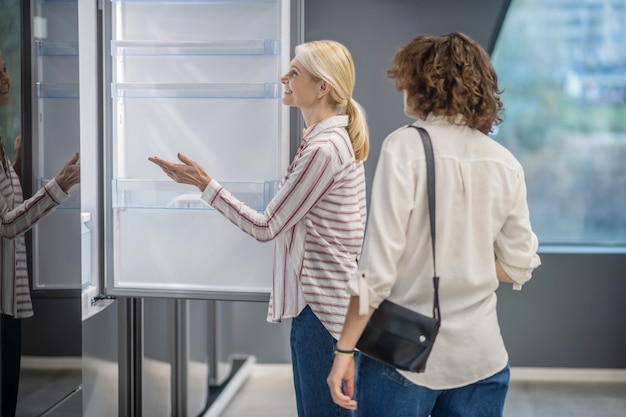 Asystent i klient. sprzedawca w pasiastej koszuli pokazuje klientowi nową lodówkę