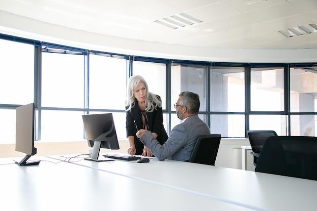 Asystent instruujący szefa. koledzy stoją i siedzą przy stole z monitorem i dokumentami, kierownik wskazuje na papier i słucha współpracownika. koncepcja komunikacji biznesowej
