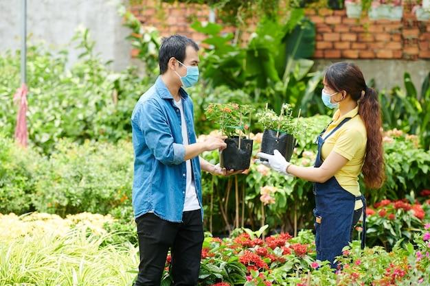 Asystent klienta i sprzedaży centrum ogrodniczego omawia kwitnące kwiaty idealne na podwórko
