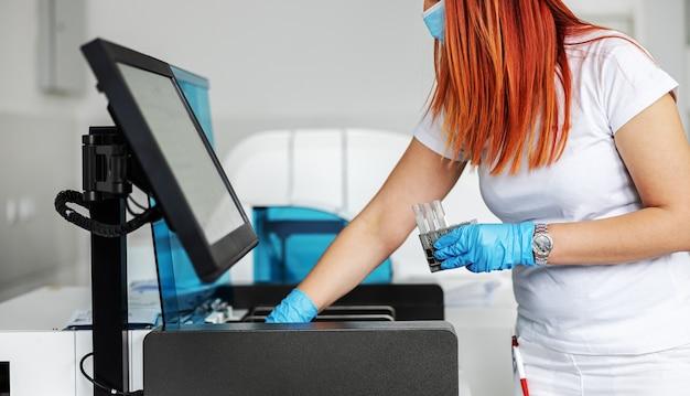Asystent laboratoryjny trzymający próbki krwi i sprawdzający, czy jest covid-19 pozytywny.