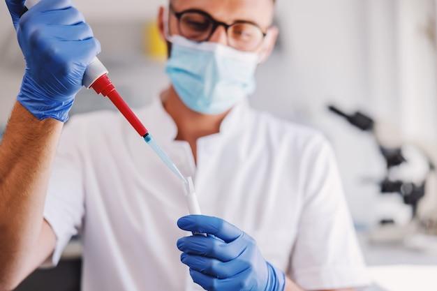 Asystent laboratoryjny w gumowych rękawiczkach i masce na twarz, trzymając probówkę z krwią i prowadzący badania