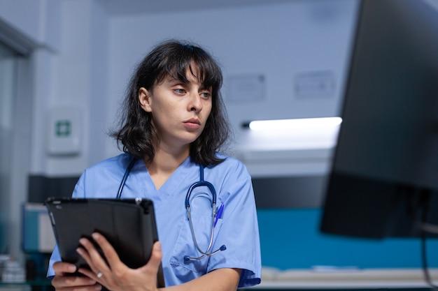 Asystent medyczny korzystający z cyfrowego tabletu z ekranem dotykowym