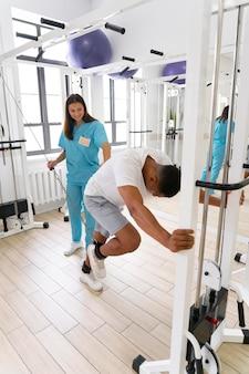 Asystent medyczny pomagający pacjentowi w ćwiczeniach fizjoterapeutycznych