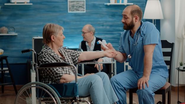 Asystent medyczny sprawdzający temperaturę niepełnosprawnej kobiety