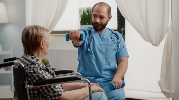 Asystent medyczny udzielający pomocy niepełnosprawnej starszej kobiecie