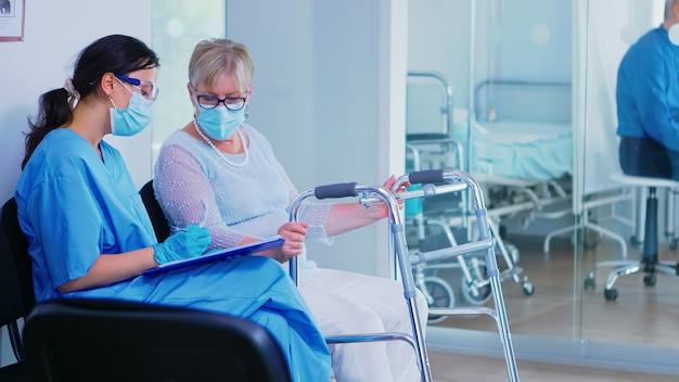 Asystent medyczny z maską na twarz przeciwko koronawirusowi w szpitalnej poczekalni, pomagając nieważnej starszej kobiecie z ramą spacerową wypełnić dokumenty. pacjent wchodzący na korytarz szpitala.