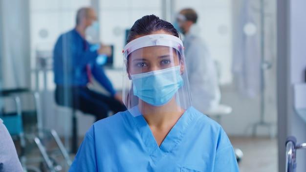 Asystent medyczny z wizjerem i maską przeciw koronawirusowi, patrząc na kamerę w poczekalni szpitala. lekarz konsultacji starszy mężczyzna w sali egzaminacyjnej.
