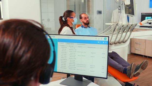 Asystent ortodonty umawiania się na wizytę za pomocą zestawu słuchawkowego siedząc na komputerze, podczas gdy lekarz pracuje z pacjentem w tle badając problem zębów. pielęgniarka pisze w gabinecie stomatologicznym