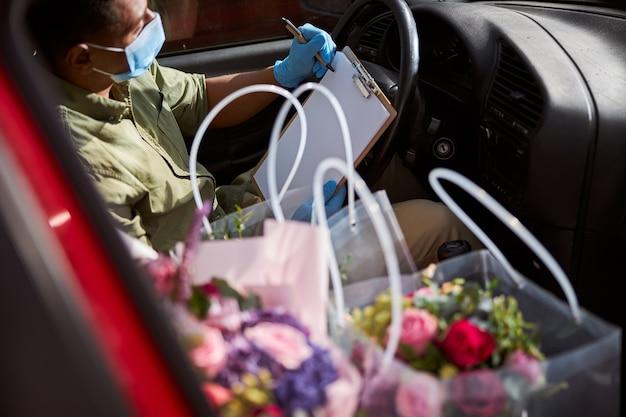 Asystent sklepu rasy mieszanej w samochodzie piszący na czystym papierze eko długopisem w pobliżu kwiatów w torebkach