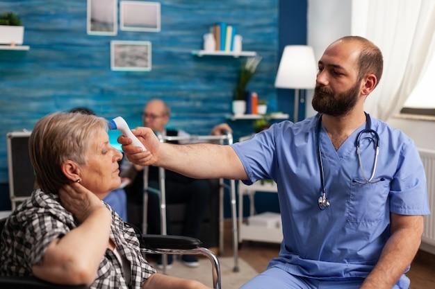 Asystent społeczny mężczyzna mierzący temperaturę niepełnosprawnej starszej kobiety za pomocą termometru medycznego na podczerwień
