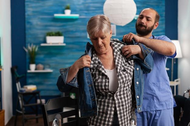 Asystent społeczny mężczyzna pracownik pomagający emerytowi niepełnosprawna starsza kobieta zakłada kurtkę