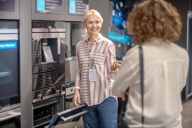 Asystent sprzedaży w koszuli w paski, pokazując klientowi nowe piece