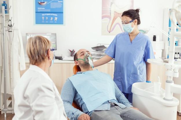 Asystent szpitalny nakłada maskę tlenową choremu pacjentowi po zabiegu stomatologicznym, siedząc na fotelu dentystycznym w sali szpitala ortodontycznego podczas konsultacji lekarskiej lekarz dentysta badający ból zęba