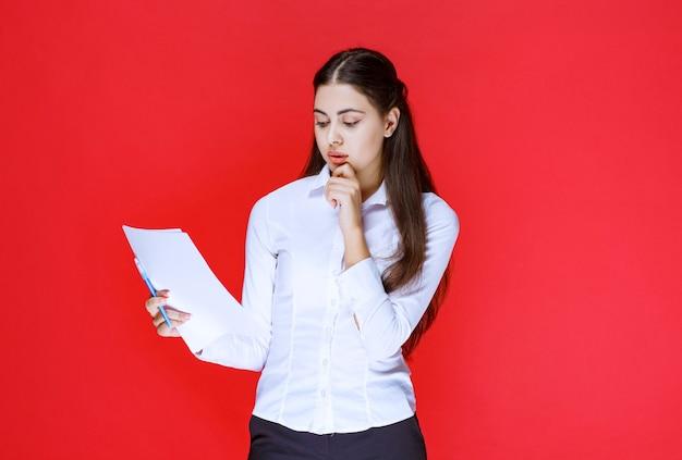 Asystent Trzymający Listy Raportów I Myślenie. Premium Zdjęcia