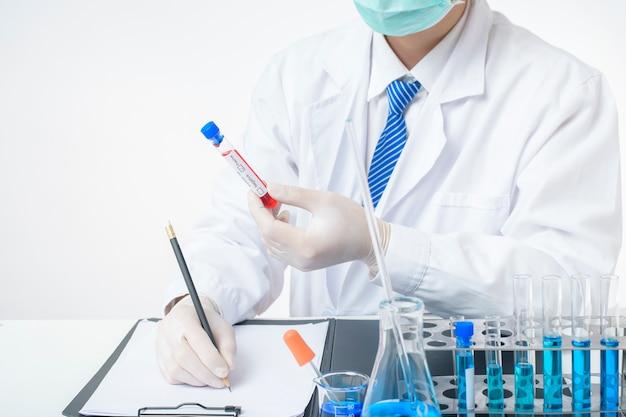 Asystent w laboratorium trzyma zainfekowanego covid-19 badania krwi