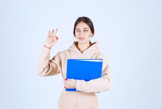 Asystent z niebieskim folderem przedstawiającym znak przyjemności