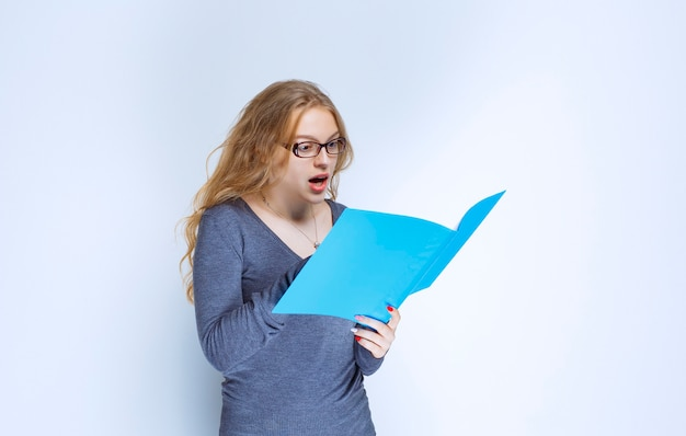 Asystent z niebieskim folderem wygląda na niezadowolonego.