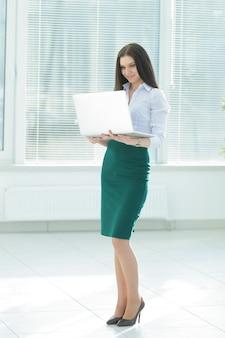 Asystent z otwartym laptopem, stojąc w biurze