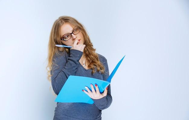 Asystentka blondynki rozmawia przez telefon, sprawdzając niebieski folder i wprowadzając poprawki.