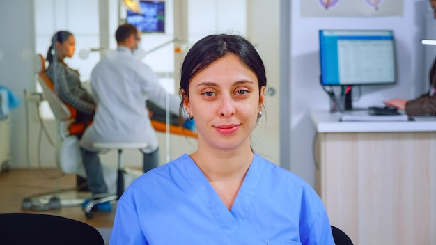 Asystentka dentystyczna patrząc na kamery, podczas gdy lekarz bada pacjenta w tle. profesjonalna pielęgniarka stomatolog uśmiechający się na kamerę internetową siedząc na krześle w poczekalni kliniki stomatologicznej.