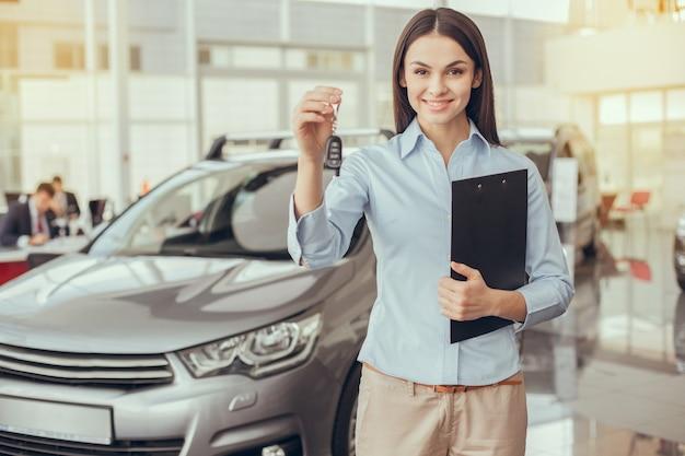 Asystentka młodej kobiety w zawodzie wypożyczalni samochodów car
