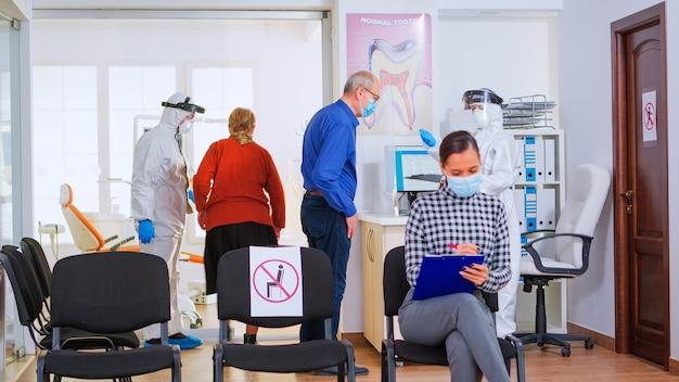 Asystentka stomatologiczna w kombinezonie przeciw koronawirusowi dająca formularz do wypełnienia po zmierzeniu temperatury pacjenta. pacjent noszący maskę ochronną na twarzy piszący na dowodzie rejestracyjnym w klinice stomatologicznej