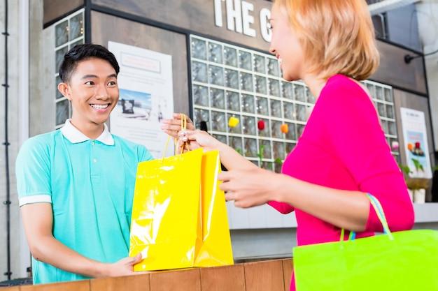 Asystentka w sklepie przekazująca zakup kobiecie