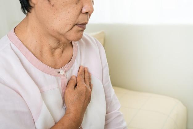 Atak serca starej kobiety mienia klatka piersiowa w łóżkowym pokoju, opieka zdrowotna problem starszy pojęcie