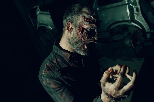 Atakujący mężczyzna zombie. koncepcja halloween. makijaż skóry i zakrwawionej twarzy