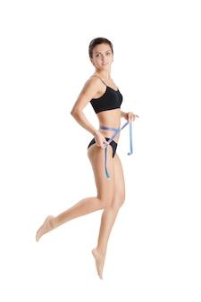 Athletic kobieta mierzy jej talię niebieską taśmą mierniczą po diecie na białym