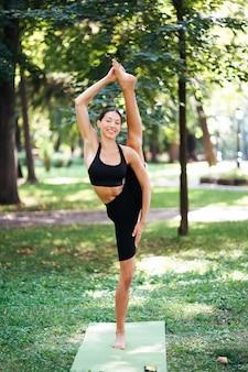 Athletic młoda kobieta robi joga w parku w godzinach porannych.