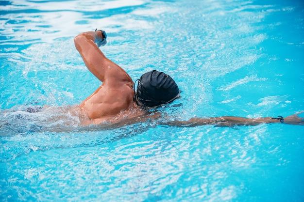 Athletic młody człowiek pływanie z tyłu przeszukiwać w basenie. zawody pływackie.