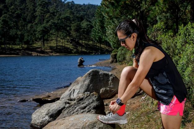 Atleta atandose las agujetas de los tenis a la orilla de un lago despues de correr en la naturaleza