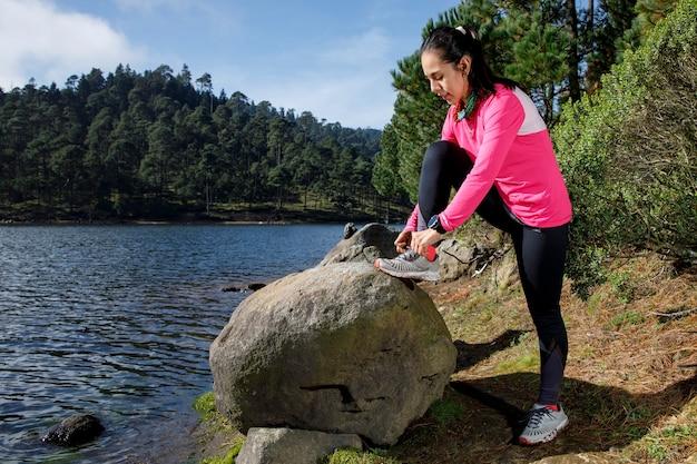 Atleta atandose los cordones de los tenis a la orilla de un lago despues de correr