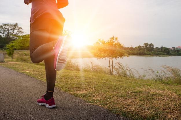 Atleta biegacza cieki biega na drogowym zbliżeniu na bucie.