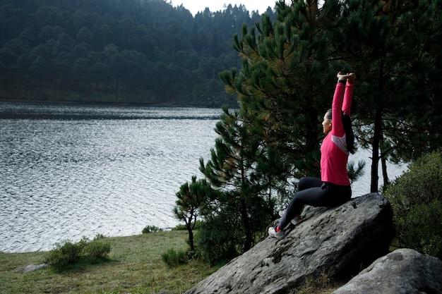 Atleta estirando despues de correr a la orilla de un lago sentada en una piedra rodeada de arboles