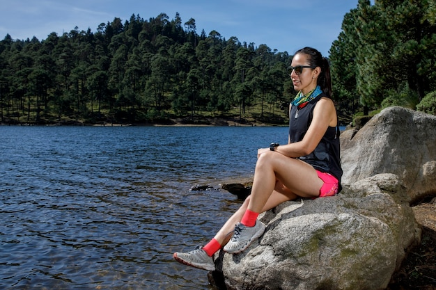 Atleta femenino descansando sobre una roca a la orilla de un lago despus de correr en el bosque