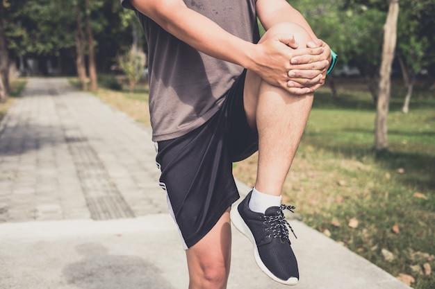 Atleta mężczyzna robi niektóre rozciąganiu ćwiczy nogi przed biegać na plenerowym