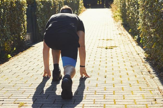 Atleta mężczyzna w bieg kuca początek pozę w świetle słonecznym