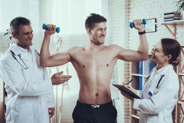 Atleta z dumbbells w klinika pokoju.