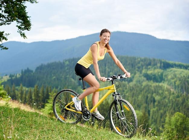 Atlety dziewczyny rowerzysty szczęśliwy kolarstwo na rowerze górskim na trawiastym wzgórzu, cieszy się letniego dzień w górach