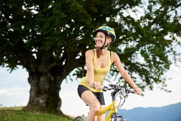 Atlety dziewczyny szczęśliwy cyklista jedzie na żółtym rowerze górskim pod dużym drzewem, cieszy się letniego dzień w górach