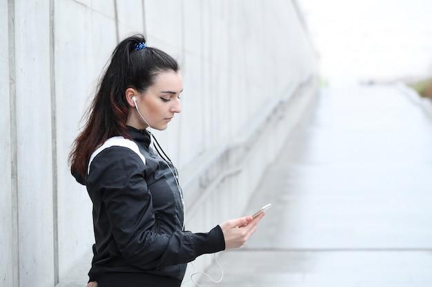 Atlety kobieta patrzeje jej smartphone