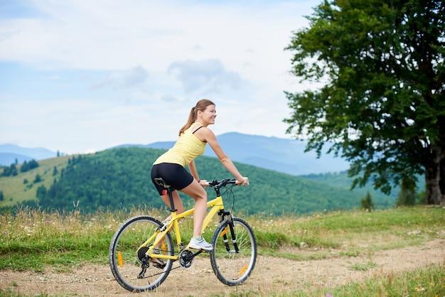 Atlety kobiety szczęśliwy cyklisty kolarstwo na żółtym rowerze górskim, cieszy się letniego dzień w górach.